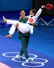 Australia's Lauren Burns celebrates her win in the final of the women's 49 kilogram Taekwondo division, in the arms of her coach Jin Tae Jeong, at the Olympic Games in Sydney Wednesday September 27, 2000. Burns defeated Urbia Melendez Rodriguez of Cuba to take the gold medal. (AP Photo/Russell McPhedran)